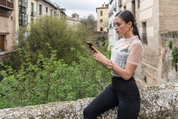 Pretty young caucasian brunette woman looking at smartphone in black and white clothes