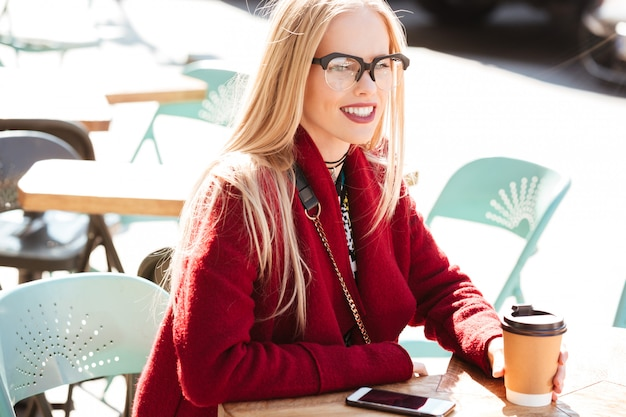 Pretty young caucasian lady sitting in cafe outdoors drinking coffee