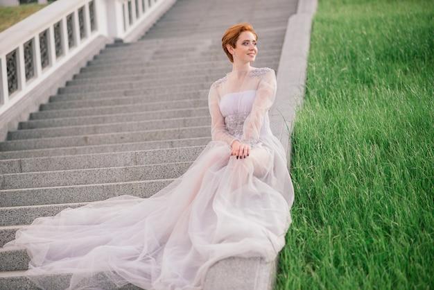 庭と彼女のウェディングブーケの外でかなり若い白人赤毛の女の子。美しい赤毛の花嫁。