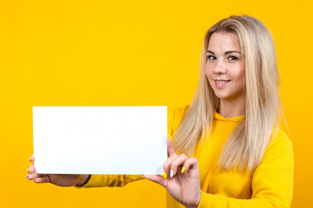 Pretty young caucasian woman holding empty blank board for advertisement.