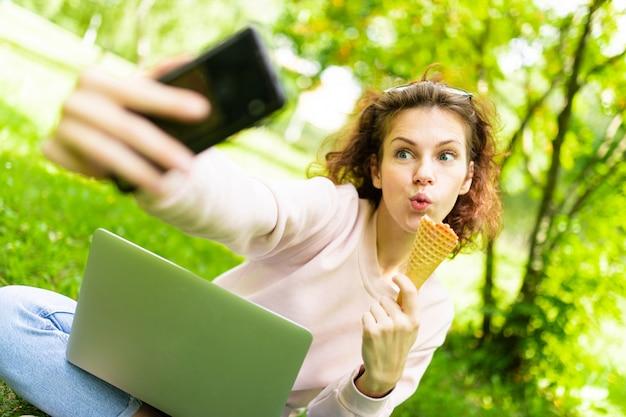 Довольно молодая кавказская женщина занимается фрилансом в парке с ноутбуком, чашкой кофе и мороженым, сидит на траве и делает селфи