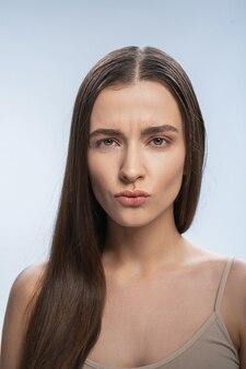 Довольно молодая кавказская женщина делает лица в камеру