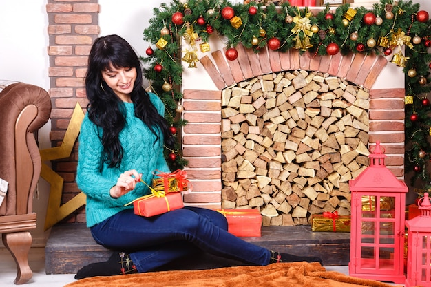 Pretty young caucasian woman sitting near a decorative fireplace with christmas decoration