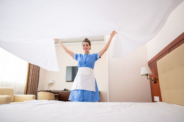 Pretty young chamber maid in uniform stretching white clean linen over bed while working in hotel room