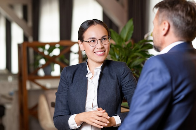 Pretty young cheerful agent in formalwear and eyeglasses looking at business partner or client during working discussion