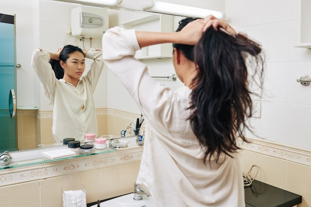 Pretty young chienese woman in white shirt making high ponytail in front of mirror in bathroom Premium Photo