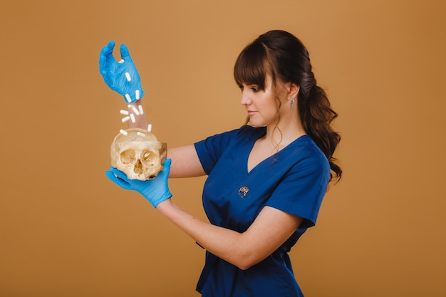 꽤 젊은 집중 연습생 소녀가 일회용 장갑을 낀 손에서 두개골에 알약을 쏟습니다.