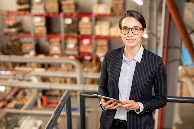 工場での作業中にタブレットを使用して技術情報を検索する正装でかなり若い自信を持って女性実業家