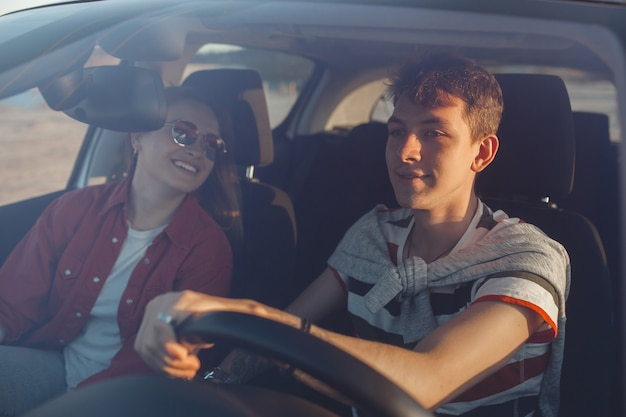 Pretty young couple driving the car at sea shore. woman and man having fun at the trip. people traveling on automobile.