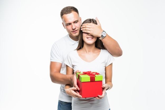 Pretty young couple man give his lady red giftbox surprise isolated on white