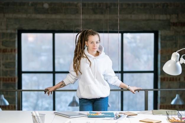 Довольно молодой креативный дизайнер в белой толстовке с капюшоном и синих джинсах стоит на рабочем месте перед камерой