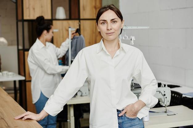 机のそばの仕立て屋の背景にワークショップでカメラの前に立っている白いシャツのかなり若い創造的なファッションデザイナー