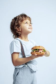 Pretty young curly boy in casual clothes on white studio wall. eating burger