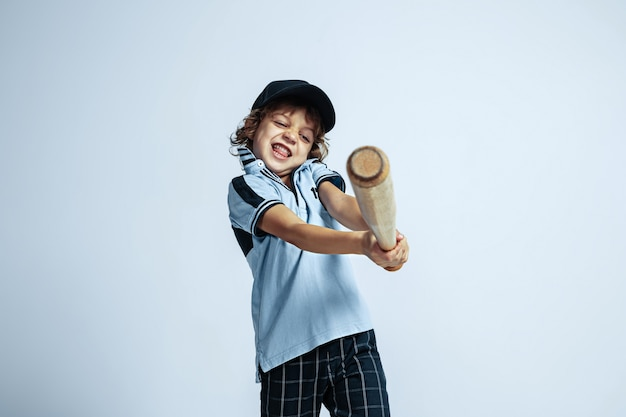 Pretty young curly boy in casual clothes on white  wall. confident and cool with sport bat. caucasian male preschooler with bright facial emotions. childhood, expression, having fun.
