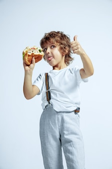 Ragazzo abbastanza giovane riccio in abbigliamento casual sulla parete bianca. mangiare hamburger. bambino in età prescolare maschio caucasico con emozioni facciali luminose. infanzia, espressione, divertimento, fast food. mostra pollice in su.