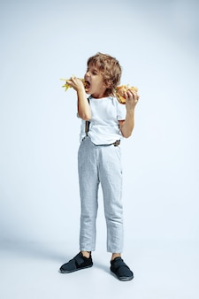 Pretty young curly boy in casual clothes on white wall. eating burger with fried potato. caucasian male preschooler with bright facial emotions. childhood, expression, fun, fast food.