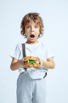 白いスタジオの壁にカジュアルな服を着たかなり若い巻き毛の少年。ハンバーガーを食べる