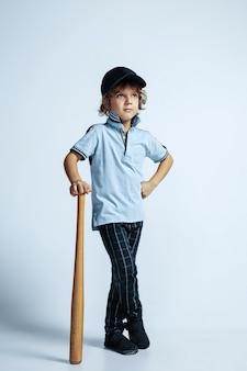 Довольно молодой кудрявый мальчик в повседневной одежде на белой стене. уверенно и круто со спортивной битой. кавказский дошкольник мужского пола с яркими эмоциями на лице. детство, самовыражение, веселье.