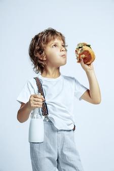 白い壁にカジュアルな服を着たかなり若い巻き毛の少年。ハンバーガーを食べる。明るい顔の感情を持つ白人男性の未就学児。子供の頃、表現、楽しさ、ファーストフード。夢のような見上げる。