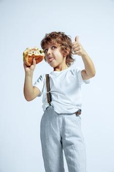 白い壁にカジュアルな服を着たかなり若い巻き毛の少年。ハンバーガーを食べる。明るい顔の感情を持つ白人の男性未就学児。子供時代、表現、楽しい、ファーストフード。親指を立てています。