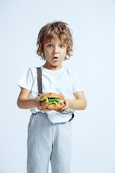 白い壁にカジュアルな服を着たかなり若い巻き毛の少年。ハンバーガーを食べる。明るい顔の感情を持つ白人男性の未就学児。子供の頃、表現、楽しんで、ファーストフード。びっくりしました。
