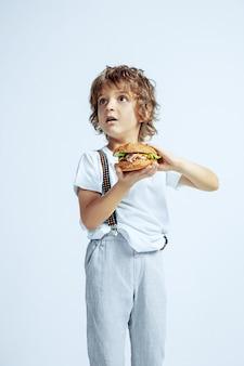 Довольно молодой кудрявый мальчик в повседневной одежде на белой стене. есть гамбургер. кавказский дошкольник мужского пола с яркими эмоциями на лице. детство, самовыражение, развлечения, фастфуд. пораженный.