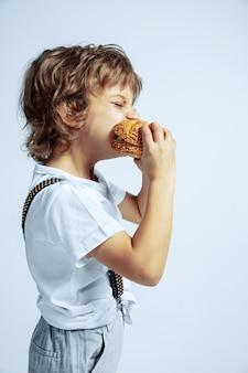 白い壁にカジュアルな服を着たかなり若い巻き毛の少年。ハンバーガーを食べる。明るい顔の感情を持つ白人男性の未就学児。子供の頃、表現、楽しんで、ファーストフード。空腹。