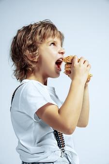 Довольно молодой кудрявый мальчик в повседневной одежде на белой стене. есть гамбургер. кавказский дошкольник мужского пола с яркими эмоциями на лице. детство, самовыражение, развлечения, фастфуд. голодный.