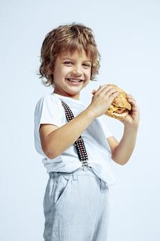 白い壁にカジュアルな服を着たかなり若い巻き毛の少年。ハンバーガーを食べる。明るい顔の感情を持つ白人男性の未就学児。子供の頃、表現、楽しんで、ファーストフード。笑顔。