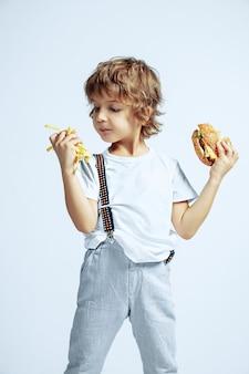 白い壁にカジュアルな服を着たかなり若い巻き毛の少年。フライドポテトと一緒にハンバーガーを食べる。明るい顔の感情を持つ白人の男性未就学児。子供時代、表現、楽しい、ファーストフード。