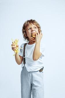 白い壁にカジュアルな服を着たかなり若い巻き毛の少年。フライドポテトと一緒にハンバーガーを食べる。明るい顔の感情を持つ白人男性の未就学児。子供の頃、表現、楽しさ、ファーストフード。