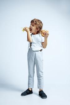 Довольно молодой кудрявый мальчик в повседневной одежде на белой стене. есть гамбургер с жареным картофелем. кавказский дошкольник мужского пола с яркими эмоциями на лице. детство, самовыражение, веселье, фастфуд.
