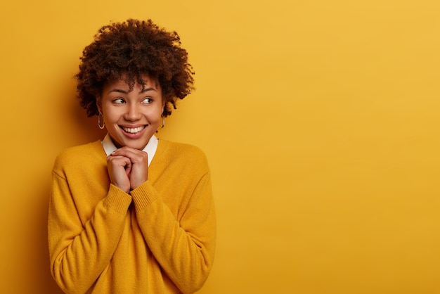 Симпатичная молодая кудрявая самочка имеет хорошее настроение, держит руки под подбородком и позитивно улыбается, смотрит в сторону, вспоминает приятные воспоминания, носит повседневный джемпер, позирует у желтой стены, пустое место справа
