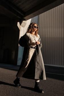 세련된 옷을 입은 선글라스를 쓴 곱슬머리 소녀는 햇빛 아래 도시에서 긴 코트를 입고 산책합니다. 어반 페미닌한 스타일과 아름다움