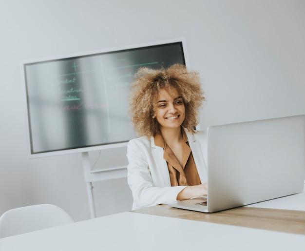 Довольно молодая женщина с вьющимися волосами, работающая на ноутбуке в ярком офисе с большим экраном позади нее