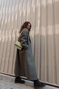 세련된 가방을 든 세련된 빈티지 롱 코트를 입은 예쁜 곱슬머리 소녀가 금속 벽 근처의 거리를 걷고 있습니다. 우아하고 여성스러운 스타일과 아름다움