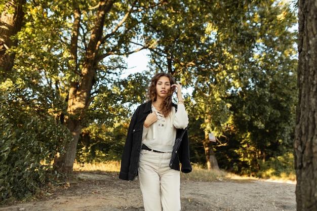 재킷과 스웨터를 입은 세련된 데님 옷을 입은 꽤 젊은 곱슬머리 여성은 자연 속에서 공원을 산책합니다. 캐주얼한 가을 여성스러운 스타일