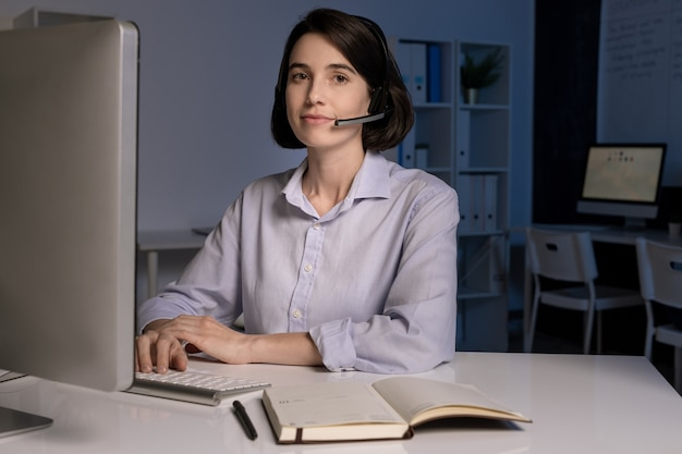 ヘッドセットを持ったかなり若いカスタマーサポート担当者がオンラインでクライアントに話しかけ、質問に答えます