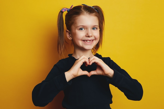 Довольно молодая милая девушка делает жест сердца, изолированные на желтом фоне