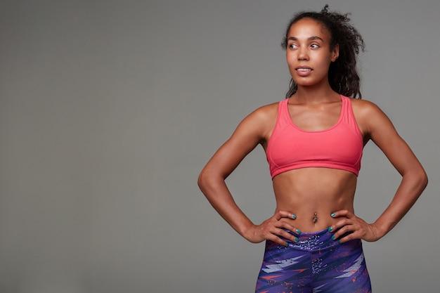 Bella giovane donna bruna dalla pelle scura vestita in abiti sportivi, guardando positivamente da parte e sorridendo leggermente, in piedi