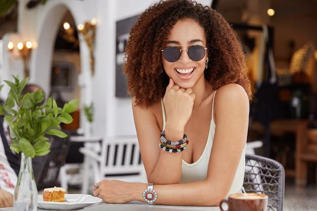 巻き毛の黒い髪、心地よい笑顔でかなり若い黒肌の女性、トレンディなサングラスをかけ、カフェのインテリアに座って、おいしいケーキを食べ、芳香族エスプレッソを飲みます。