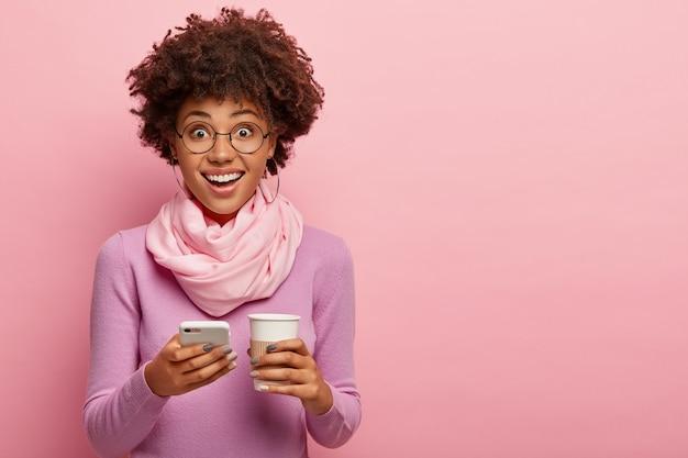 아프로 헤어 스타일로 꽤 젊은 어두운 피부를 가진 여자, 휴대 전화와 일회용 커피 한잔, 보라색 폴로 넥과 스카프를 입고 분홍색 벽 위에 포즈를 취합니다. 커뮤니케이션, 라이프 스타일, 기술