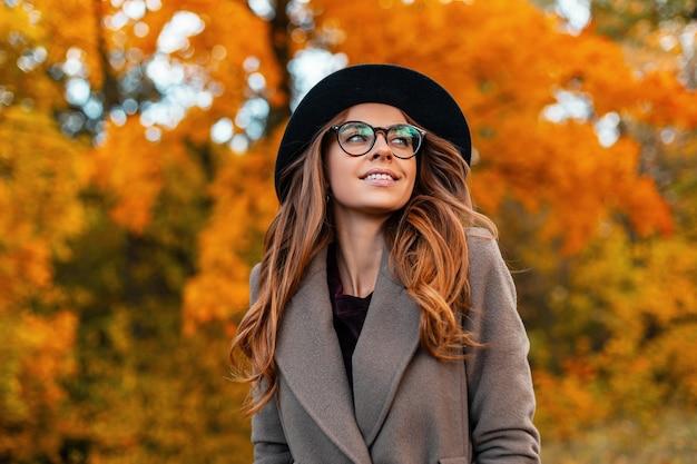 オレンジ色の葉のある木々に囲まれた公園を散歩する、美しい笑顔のコートを着たメガネをかけた豪華な帽子をかぶったかなり若いエレガントな女性モデル。森の中でポーズをとる現代の陽気な女の子のヒップスター。