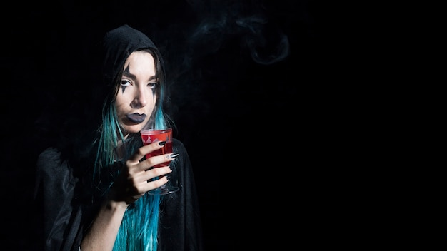 Pretty young enchantress with red goblet