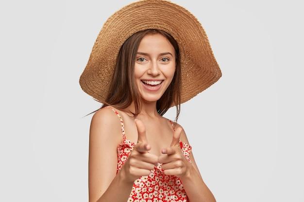 Симпатичная молодая европейская модель с зубастой улыбкой делает жест пистолетом, показывает на вас