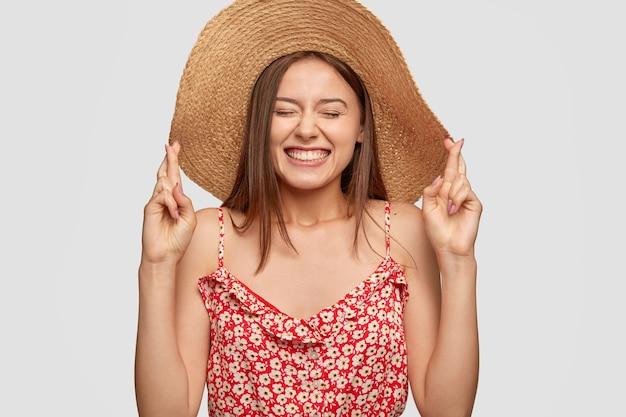Довольно молодая европейская женщина скрещивает пальцы в ожидании особого момента