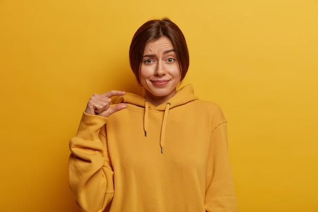 Pretty young european woman shows small size, demonstrates tiny measure, speaks about amount, dressed inn casual hoodie, shapes little object, isolated on yellow wall. body language concept.