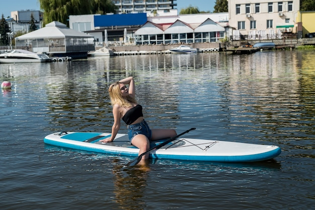 Pretty young european woman with sup board on water of river