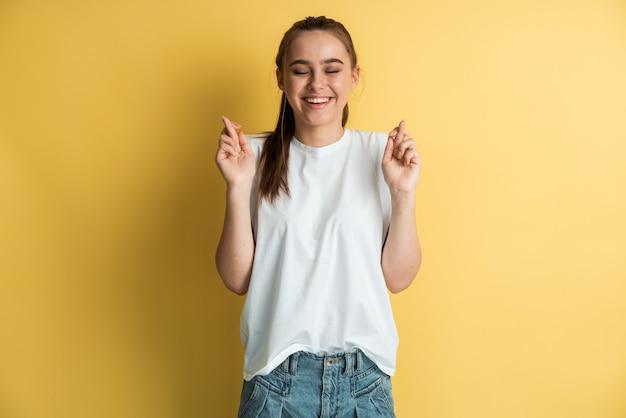 흰색 tshirt의 꽤 젊은 흥분된 여성은 그녀의 손가락을 교차하고 바람직한 소원을 만들고 노란색 배경에 좋은 소식을 기다립니다.