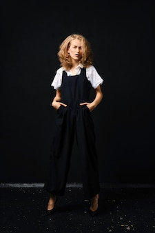 Pretty young fashion model in black pantsuit and white shirt posing over black